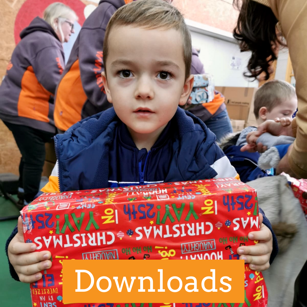 Young boy holding up a decorated shoebox as part of the Teams4U shoebox appeal