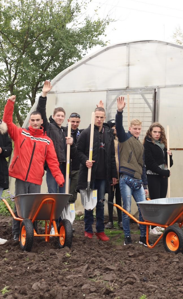 Young people standing in front of a polytunnel