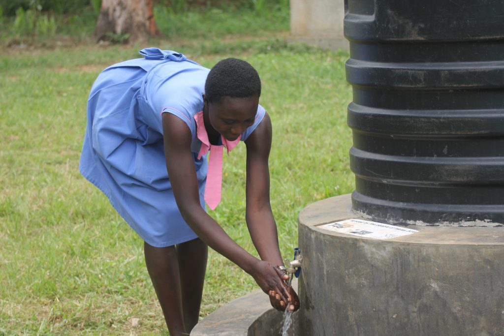 woman washing hands from tap on water tank